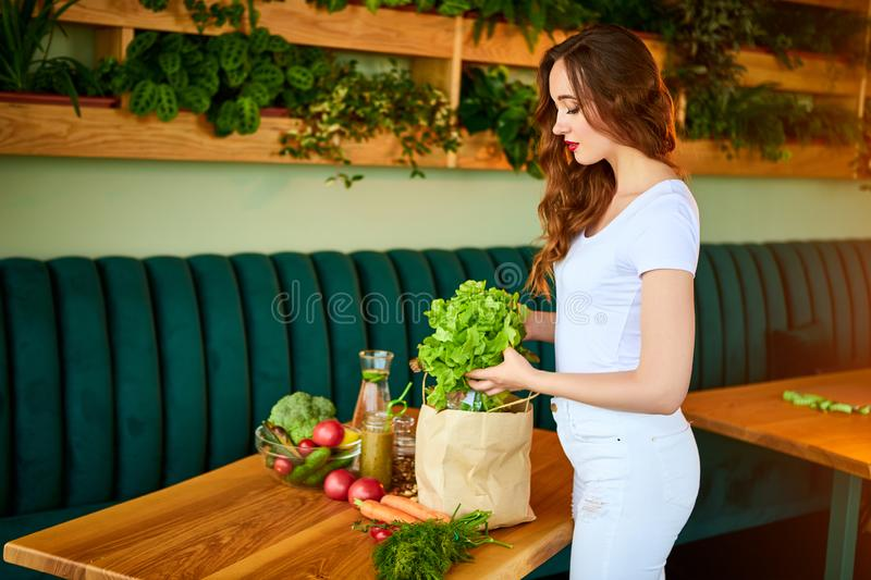 Young woman at kitchen taking out lettuce from grocery shopping paper bag with fruits and vegetables products royalty free stock image
