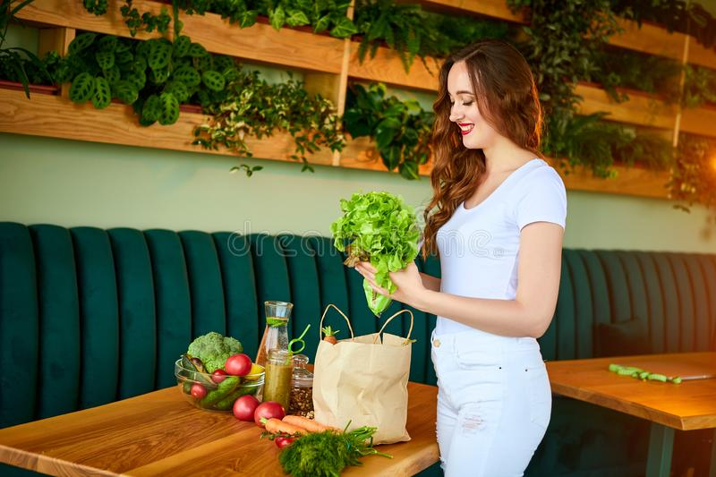 Young woman at kitchen taking out lettuce from grocery shopping paper bag with fruits and vegetables products royalty free stock photos