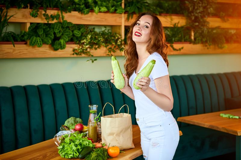 Young woman at kitchen taking out zucchini from grocery shopping paper bag with fruits and vegetables products royalty free stock images