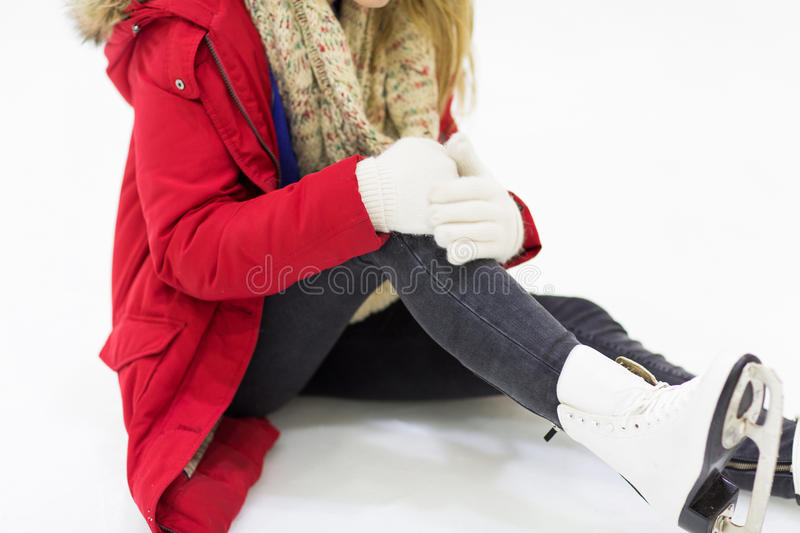 Young woman with knee trauma on skating rink. People, sport, trauma, pain and leisure concept - close up of young woman fell down on skating rink with knee stock images