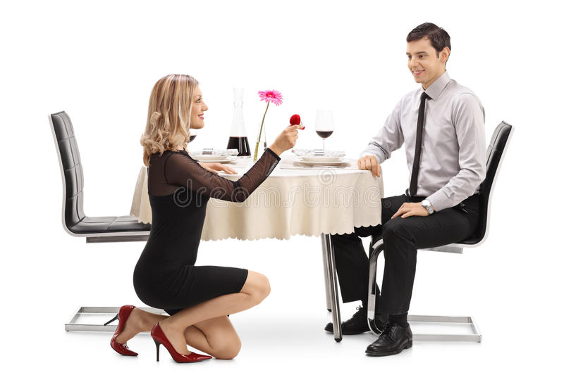 Young woman kneeling and proposing to her boyfriend. Young women kneeling and proposing to her boyfriend at a restaurant table isolated on white background stock photo