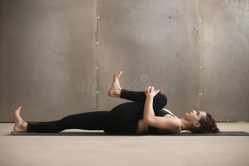 Young woman in Knees to Chest, Apanasana pose, grey studio. Young attractive sporty woman practicing yoga, stretching in Knees to Chest, Apanasana exercise royalty free stock images