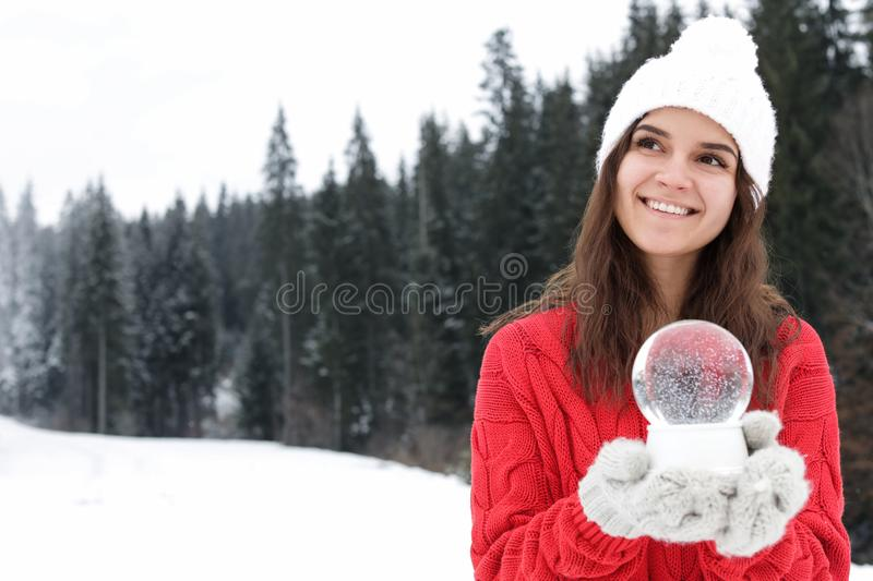 Young woman in knitted clothes holding snow globe, space for text. Winter vacation. Young woman in knitted clothes holding snow globe outdoors, space for text stock photos