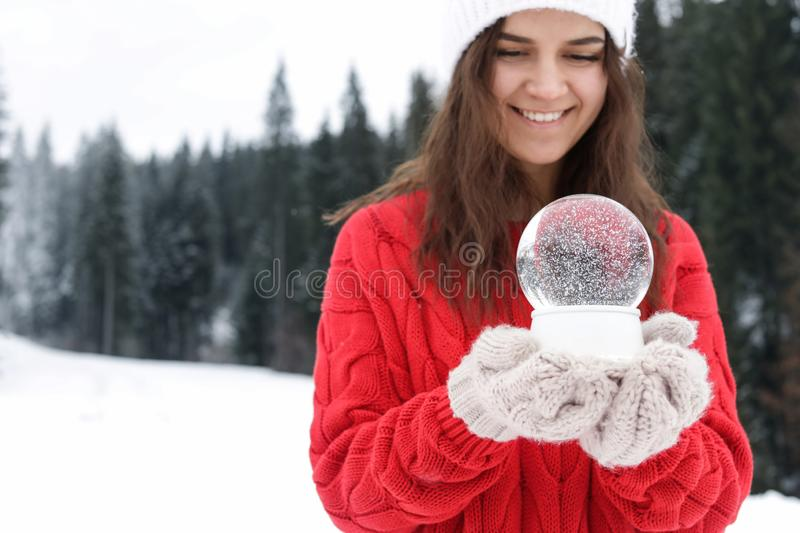 Young woman in knitted clothes holding snow globe, space for text. Winter vacation. Young woman in knitted clothes holding snow globe outdoors, space for text royalty free stock photos