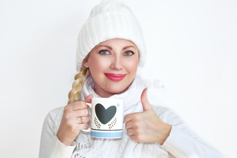 A young woman in a knitted hat and scarf holding a mug of tea and showing her thumb up. royalty free stock photos
