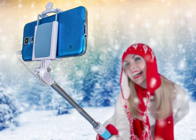 A young woman in a knitted hat scarf and mittens takes pictures of herself on the phone in a winter forest royalty free stock photography