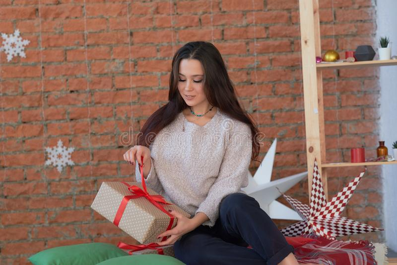 Young woman in a knitted sweater in jeans is sitting on a wooden floor near a living. Girl waiting for christmas. royalty free stock photography