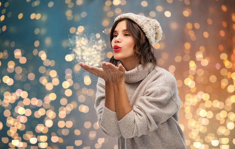 Young woman in knitted winter hat sending air kiss. Christmas, season and people concept - happy young woman in knitted winter hat and sweater sending air kiss royalty free stock images