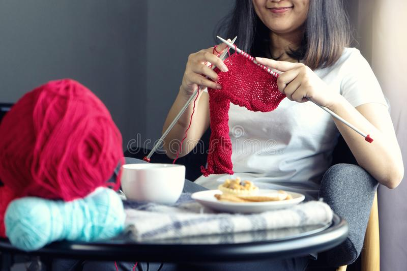 Young woman knitting for her hobby on the bed royalty free stock images