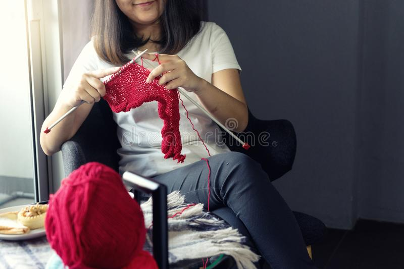 Young woman knitting for her hobby on the bed stock photo