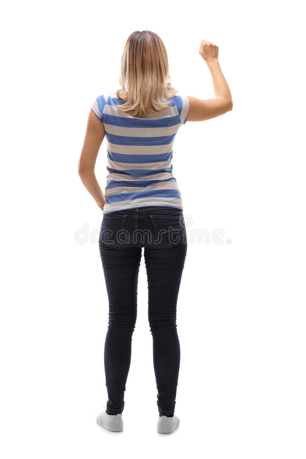 Young woman knocking on a door. Full length rear view shot of a young woman knocking on a door on white background royalty free stock photo
