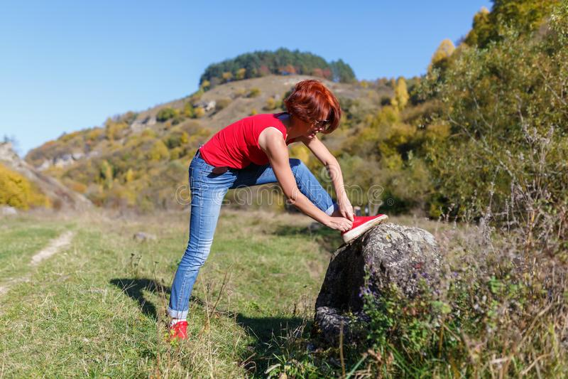 Young woman laces up the jogging shoes against the blue sky and forest after a pedestrian walk sunny day.  royalty free stock photo