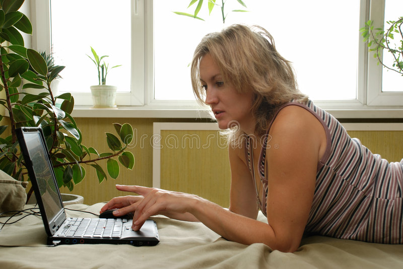 Young woman with laptop. Woman using laptop at home stock images