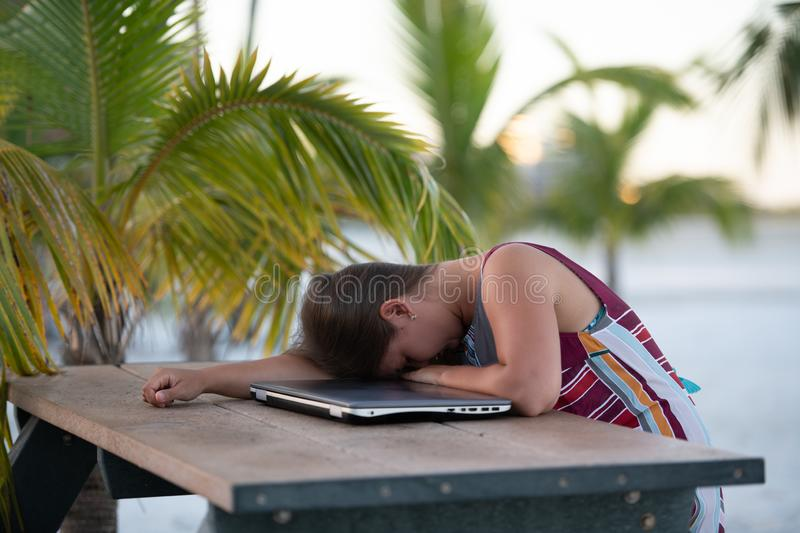 Young woman with laptop on beach. Tired and stressed young woman wearing dress sleeping by her laptop in the beach on the background of palm trees  in Florida royalty free stock photos