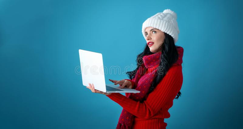 Young woman with a laptop computer holding a Christmas gift box royalty free stock photo