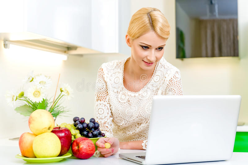 Young woman with laptop computer in the kitchen