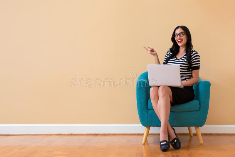 Young woman with a laptop computer pointing something. Sitting in a chair royalty free stock photo