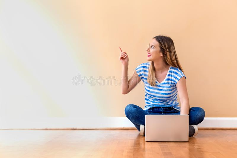 Young woman with a laptop computer pointing something royalty free stock image