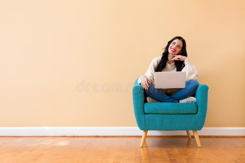 Young woman with a laptop computer in a thoughtful pose stock image