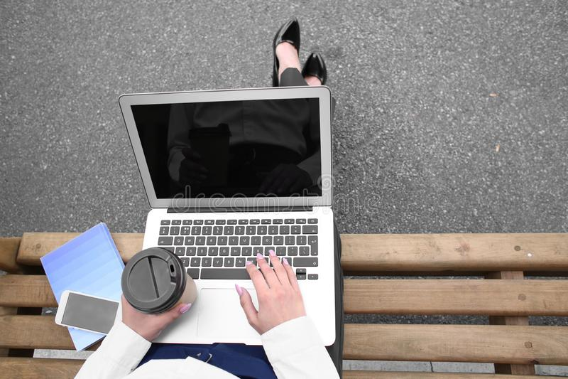 Young woman with laptop and cup of coffee resting on bench outdoors royalty free stock photos