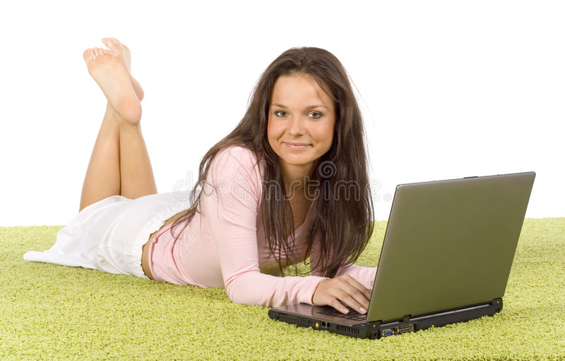 Young woman with laptop on the green carpet stock photography