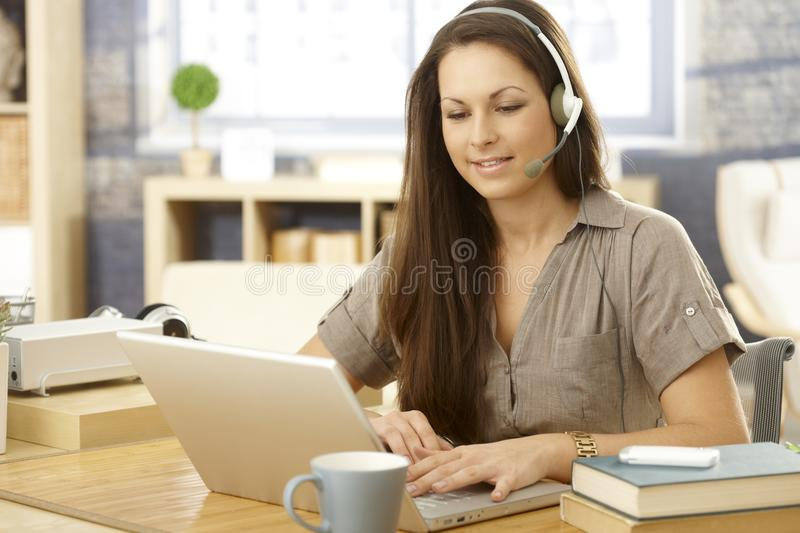 Young woman with laptop and headset royalty free stock image