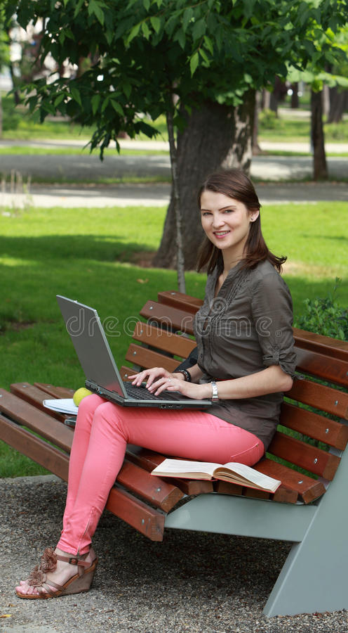 Young Woman With A Laptop In A Park Royalty Free Stock Photo