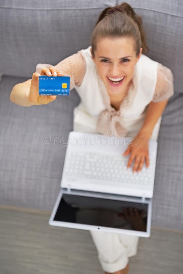 Young woman with laptop showing credit card. Happy young woman with laptop showing credit card royalty free stock photo