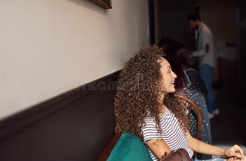 Young woman laughing while sitting with friends in a cafe stock photo