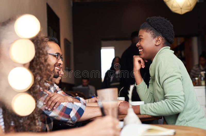Young woman laughing while talking with friends in a cafe royalty free stock photography