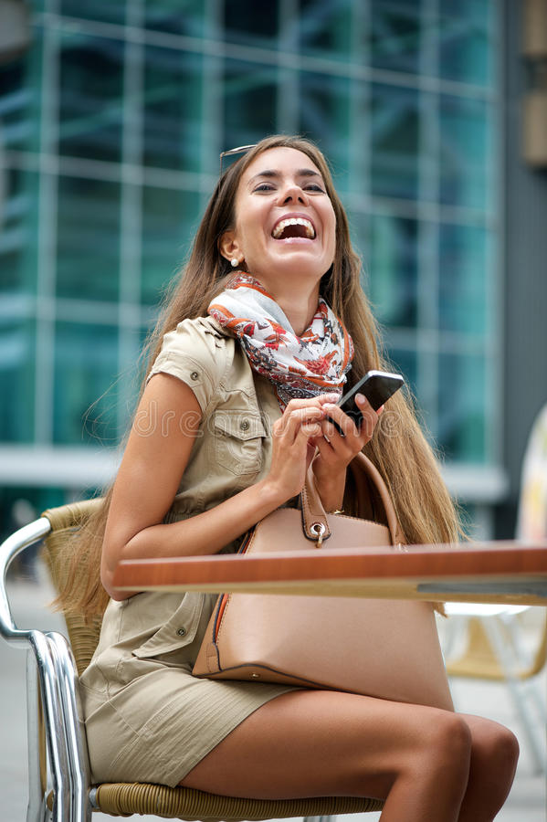 Young woman laughing at text message stock photos