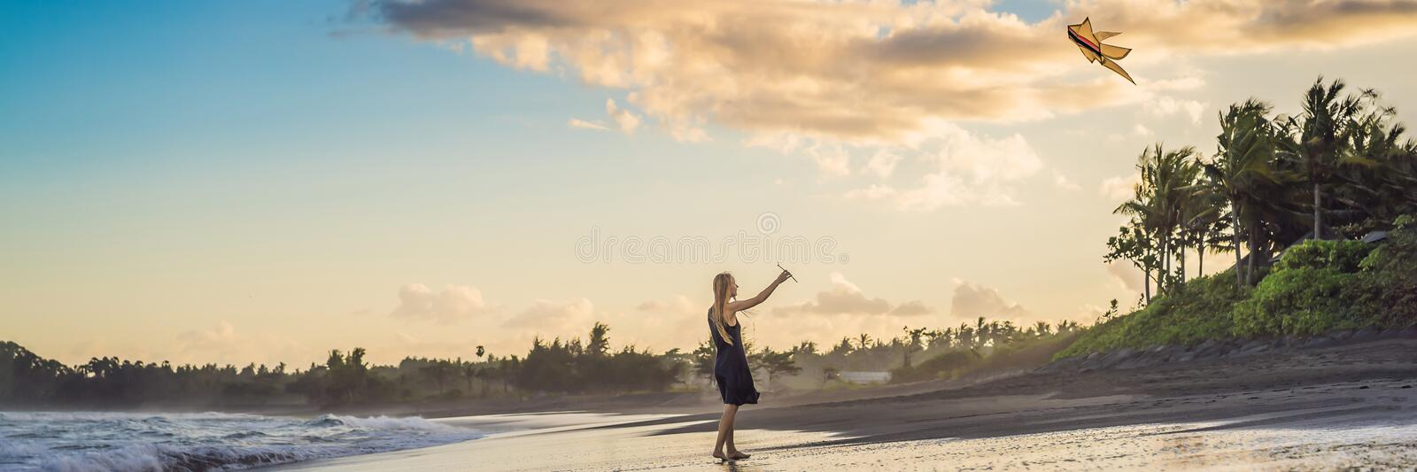 A young woman launches a kite on the beach. Dream, aspirations, future plans BANNER, LONG FORMAT. A young woman launches a kite on the beach. Dream, aspirations stock image