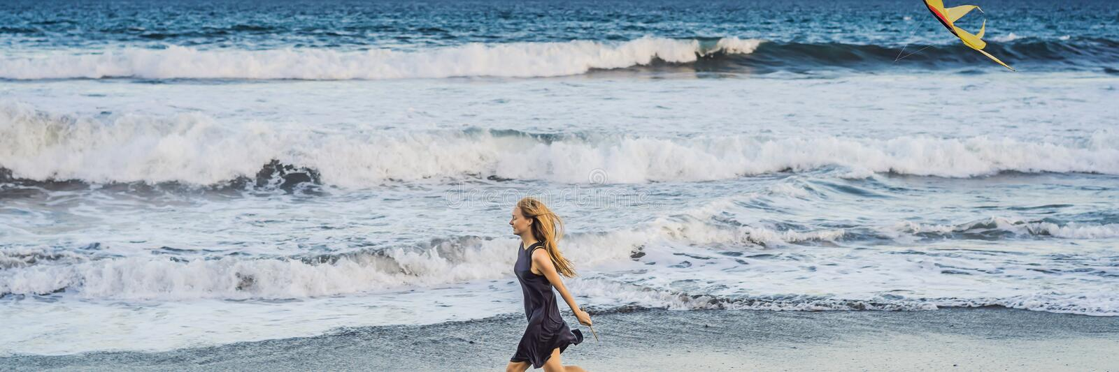 A young woman launches a kite on the beach. Dream, aspirations, future plans BANNER, LONG FORMAT royalty free stock image