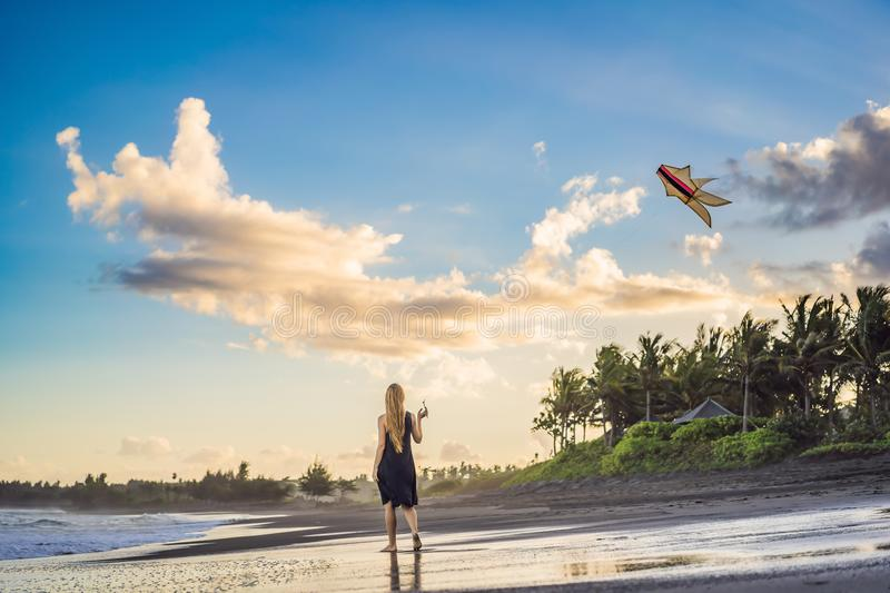 A young woman launches a kite on the beach. Dream, aspirations, future plans.  stock photography