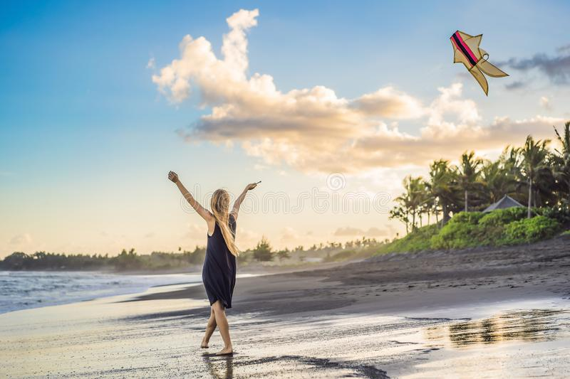 A young woman launches a kite on the beach. Dream, aspirations, future plans.  stock photos