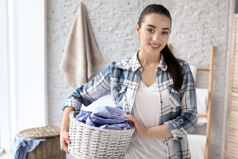 Young woman with laundry basket royalty free stock photography