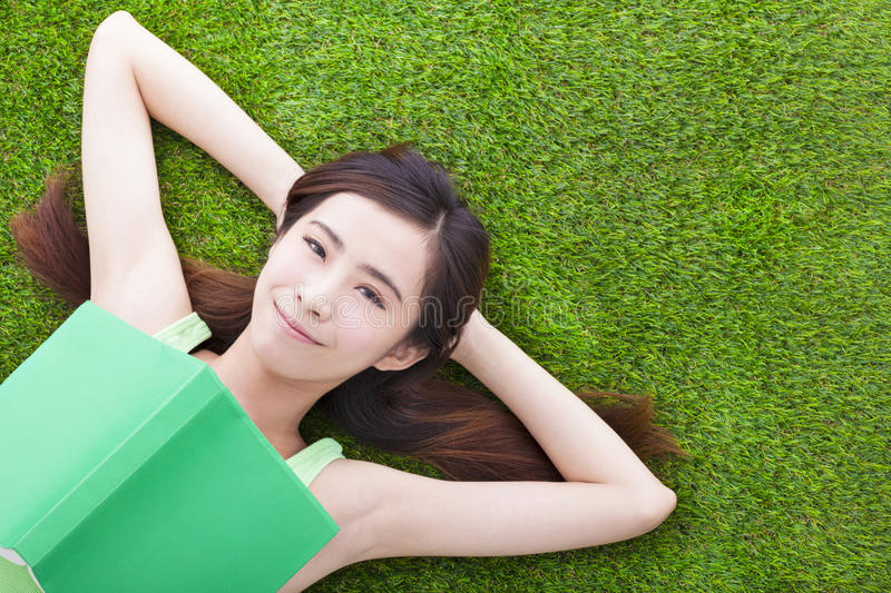 Download Young Woman Laying Down  On A Meadow With Books Stock Photo - Image: 40542447