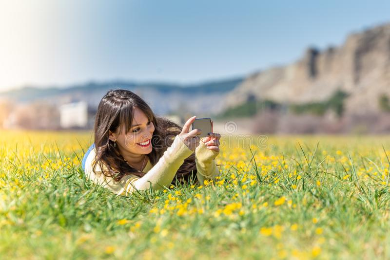 Young Woman Laying Down Using Mobile Phone stock photography
