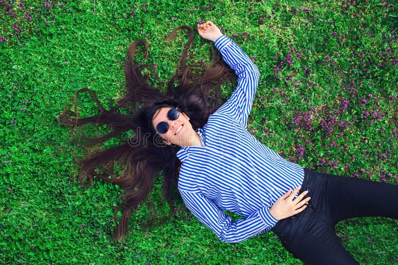 Young woman laying on green grass. royalty free stock image