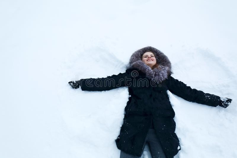 Woman making snow-angel royalty free stock image