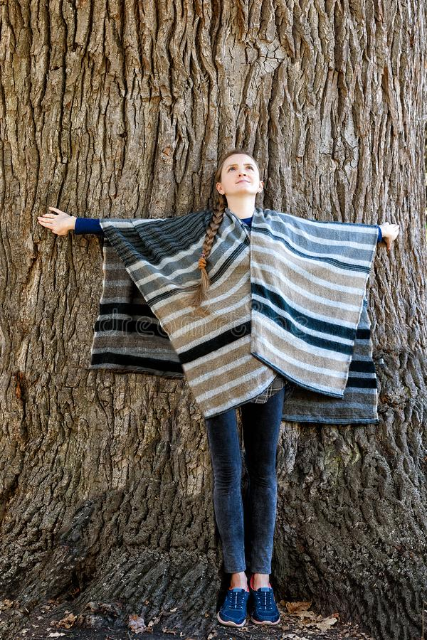 Young woman leaned her back against the trunk of a large tree. Unity with nature royalty free stock photo
