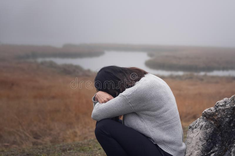 Young woman leaning against a stone with arms crossed in front of the face crying stock images
