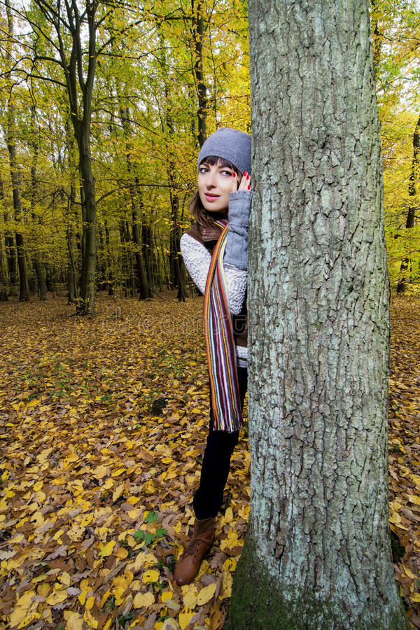 Young woman is leaning against the tree and listen to him. Young beautiful woman is leaning against the tree and listen to him stock image