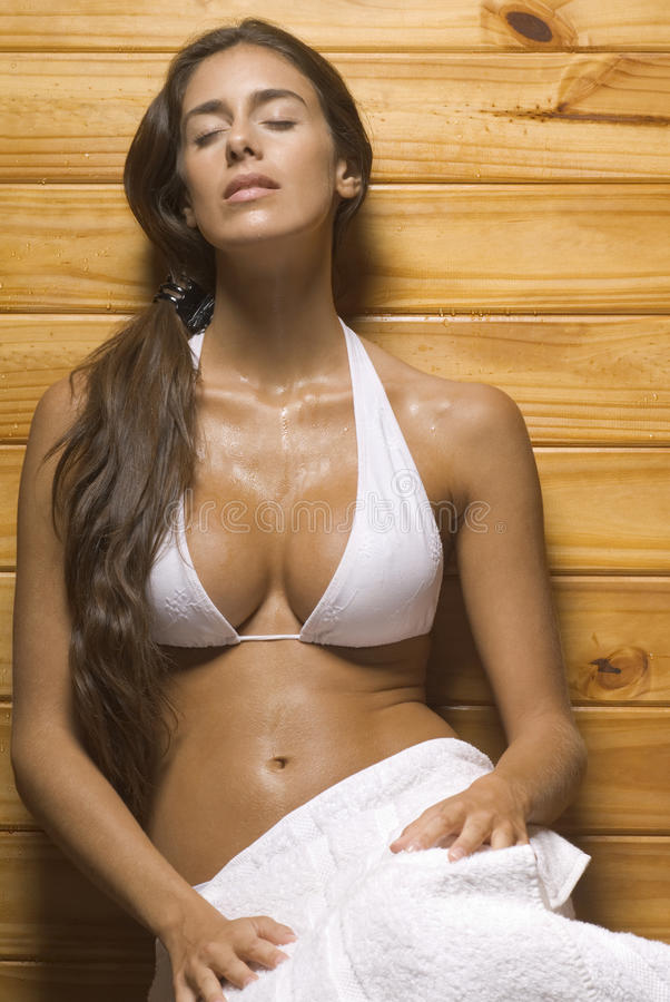 Young woman leaning against a wooden wall in a sauna stock photo