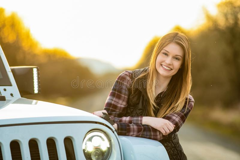 Young woman leaning on her SUV at sunset royalty free stock image