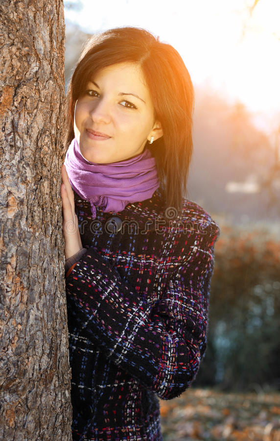 Young woman leaning to tree trunk in autumn forest. Outdoors portrait of happy young woman leaning to tree trunk in autumn forest stock photography