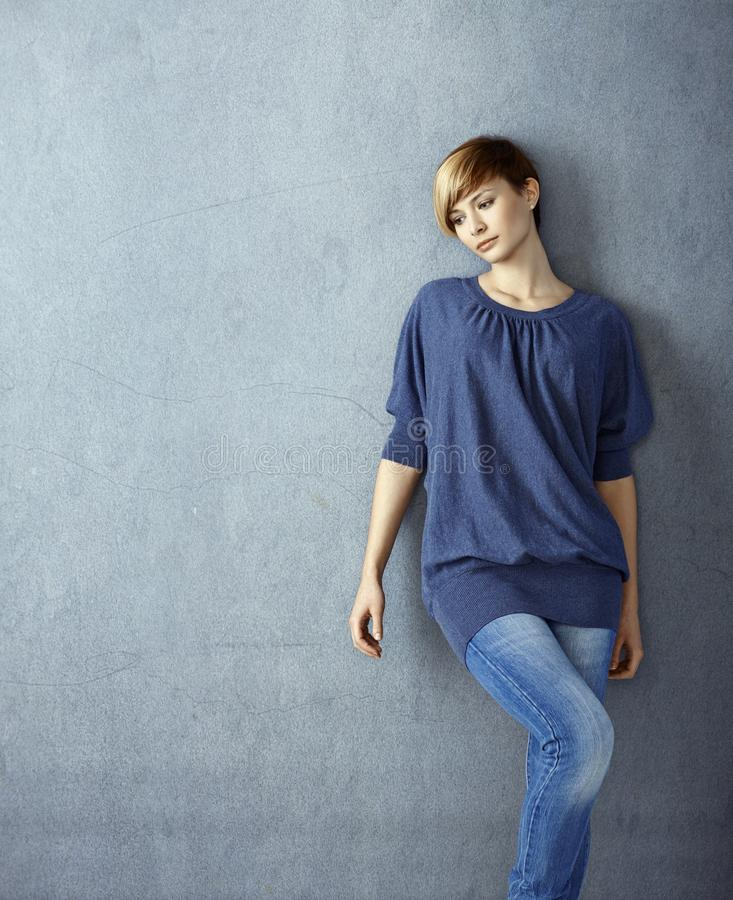 Young woman leaning to wall daydreaming stock photography