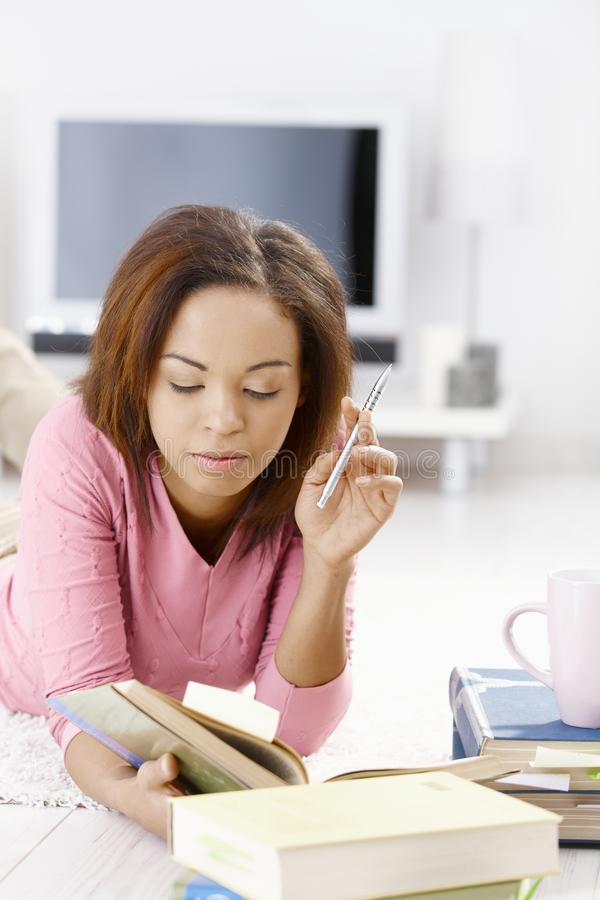 Young woman learning at home. Reading book, lying on floor, holding pen stock image