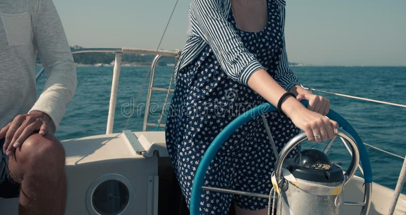 Young woman learns to control yacht on Black Sea. A young woman on the wheel of a yacht on the Black Sea stock photos