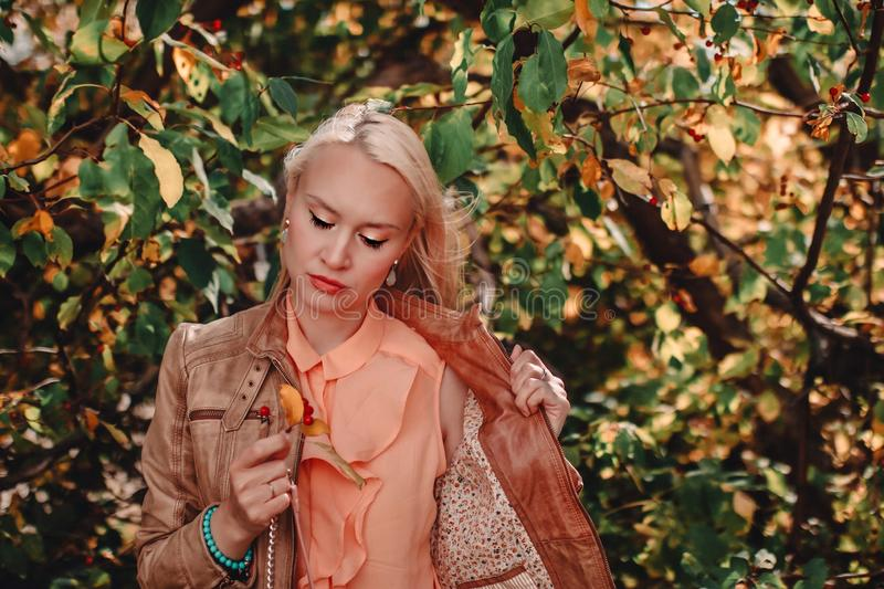 Young blonde woman with autumn leaves in hand and fall yellow and green garden background royalty free stock photography